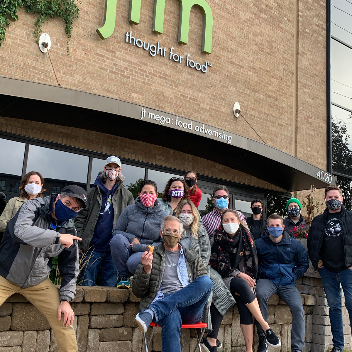 Masked creative team in front of JT Mega office